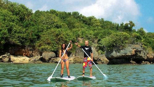 A student and instructor on stand up paddle boards in Kuta