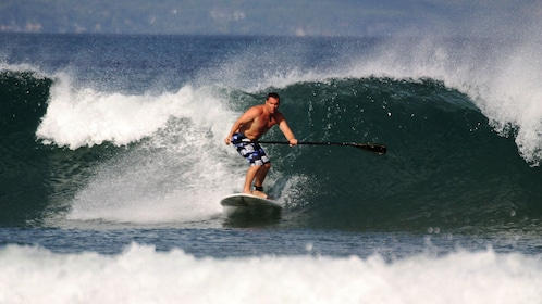 A man on a stand up paddle board riding a wave in Kuta