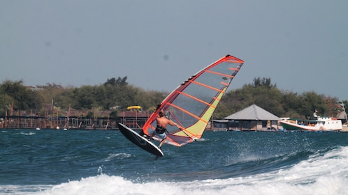 A windsurfer performing a trick in Bali