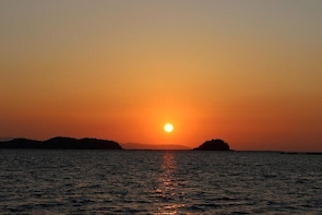 Sunset cruising around the islands while watching the 100 best sunsets in J...