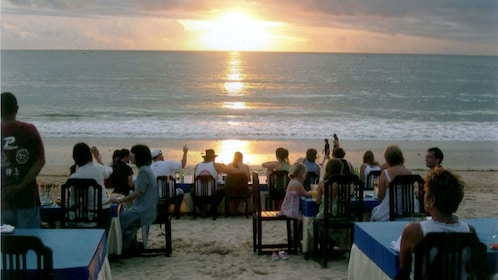Group of people eating at beachside dining tables at sunset in Bali