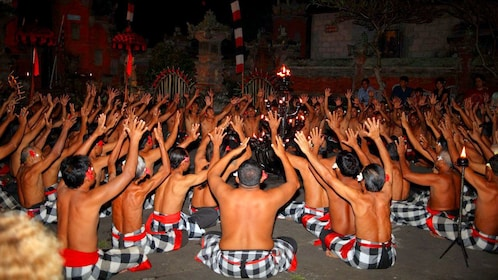 Male performers sitting with their arms raised during a Kecak Dance at Uluwatu Temple in Bali