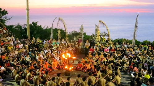 Kecak Dance performers sit around a group of torches during a performance at Uluwatu Temple in Bali