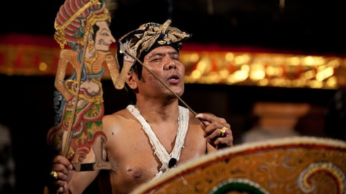 Man performing with a paper puppet in Bali