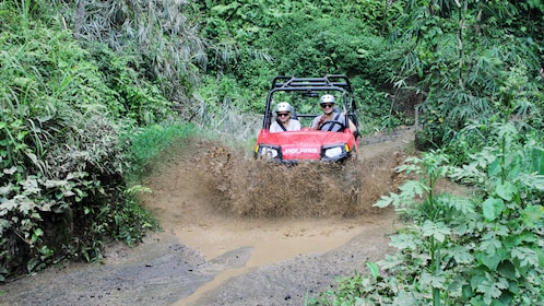 Two people in a buggy driving through a mud puddle in Bali
