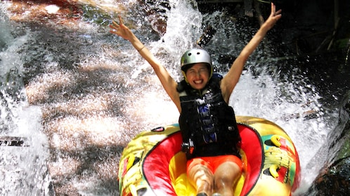 A woman tubing down a river in Bali