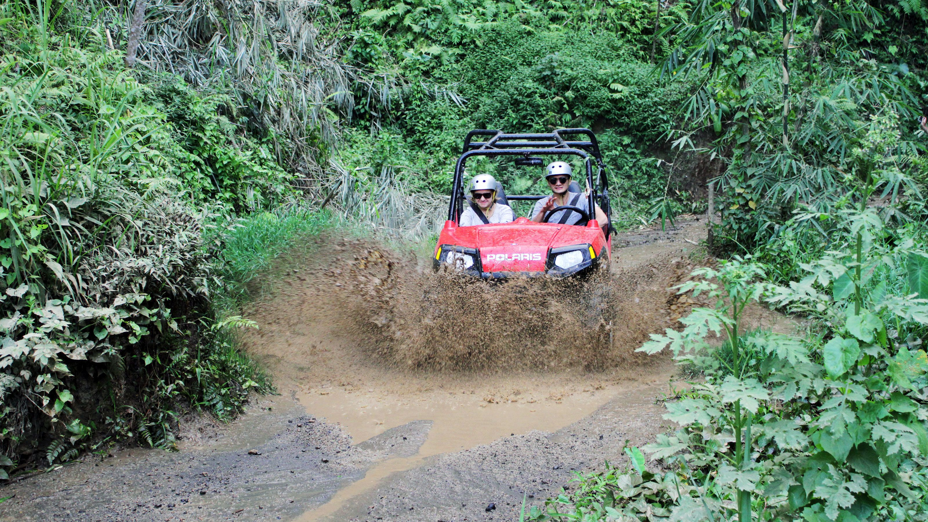 Two people in a buggy going through mud in Bali