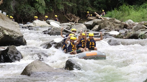 White water rafters cruising on weak current in Bali