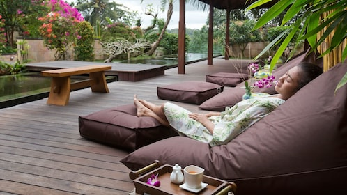 A relaxing nap on pillowed seats outdoors at a spa in Bali