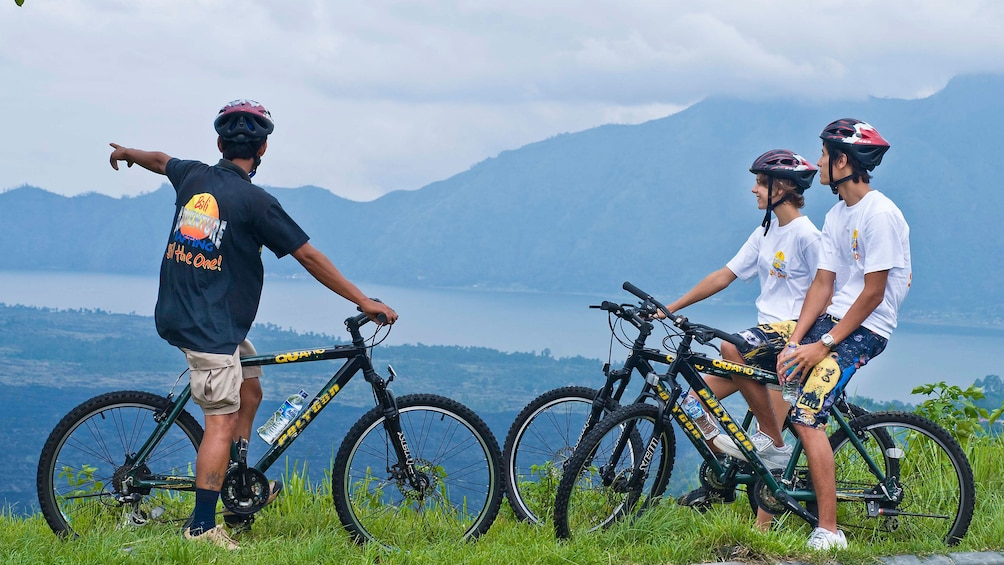 Show item 3 of 5. Bicycling group at a scenic lookout in Bali