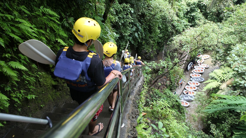 Show item 5 of 5. Rafting group walking down a staircase to the Ayung River in Bali