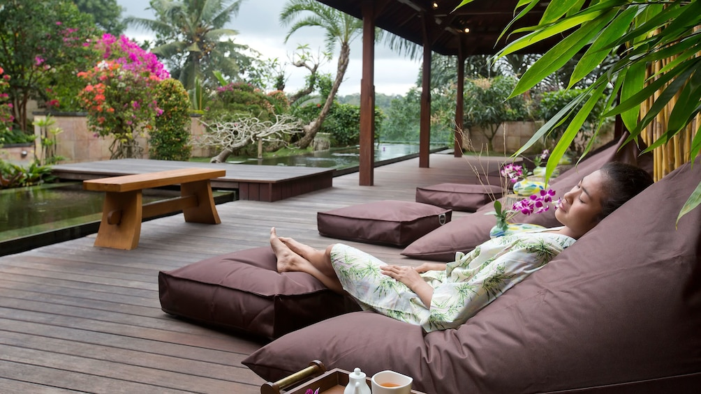 Show item 2 of 5. Woman relaxing on a deck at a spa in Bali