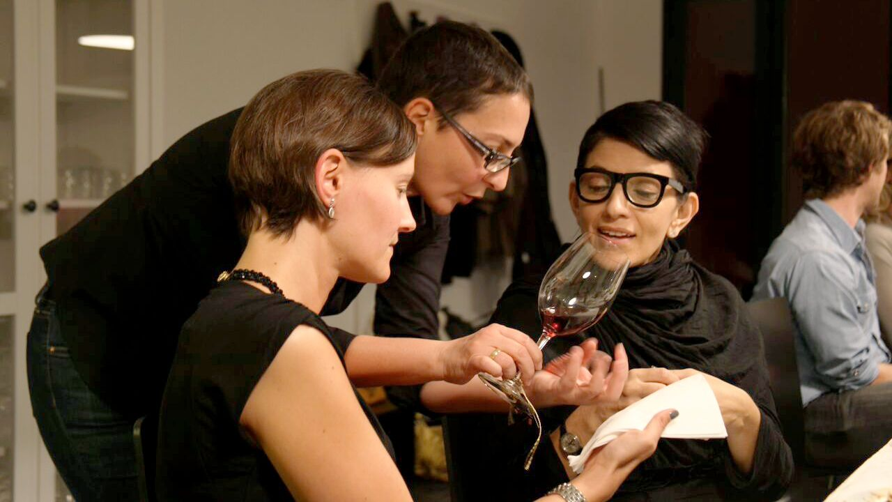 Sommelier describing wine to a pair of women at a table in Rome