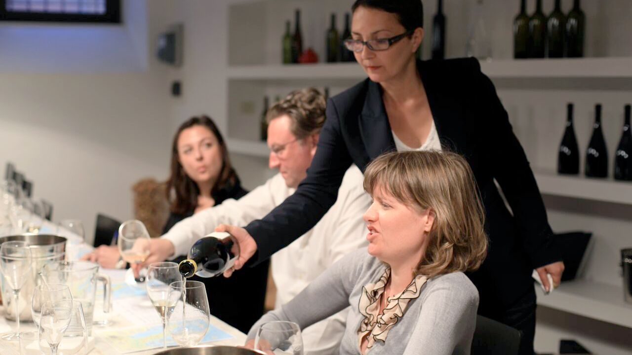 Sommelier pouring wine for a group in Rome