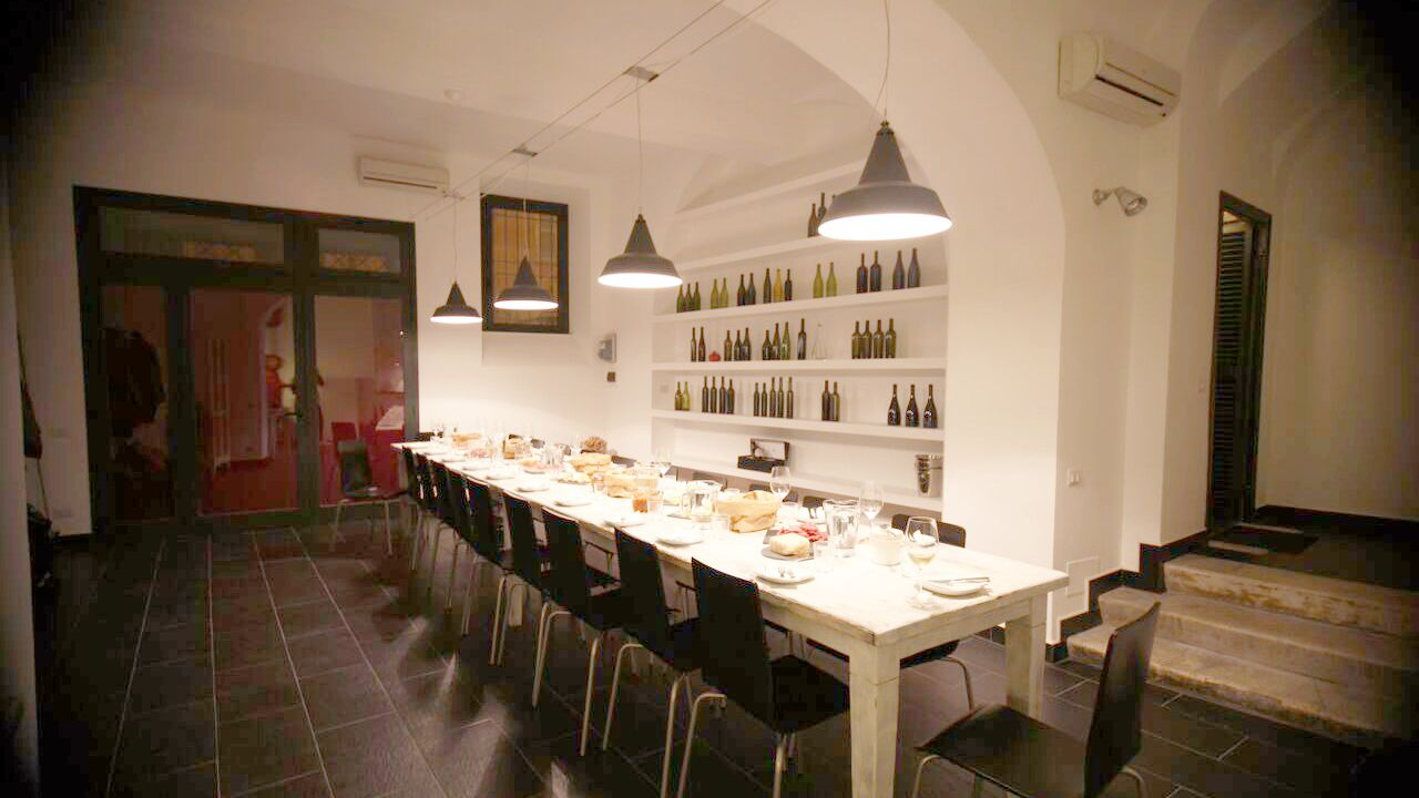 Table of food pairings and shelves of wine in Rome