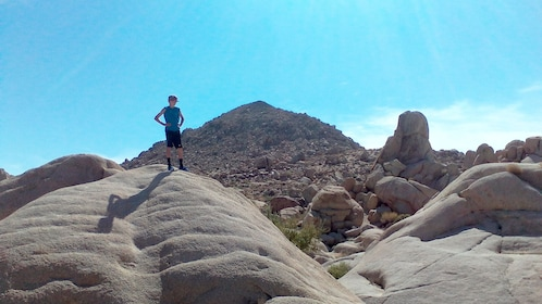 Hiking woman standing on a big rock in Palm Springs