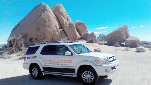 SUV parked near a large rock formation at Joshua Tree National Park in Palm Springs