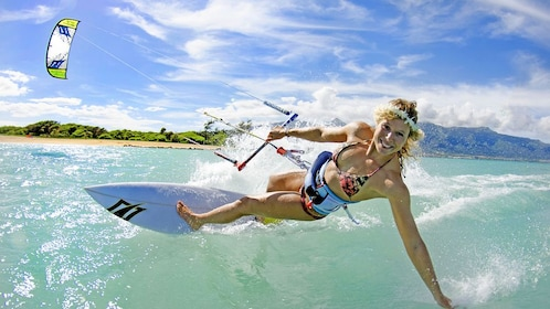 Smiling woman cresting a wave riding a kiteboard