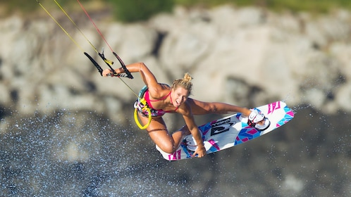 Woman looking at he camera grabs her kiteboard while airborne