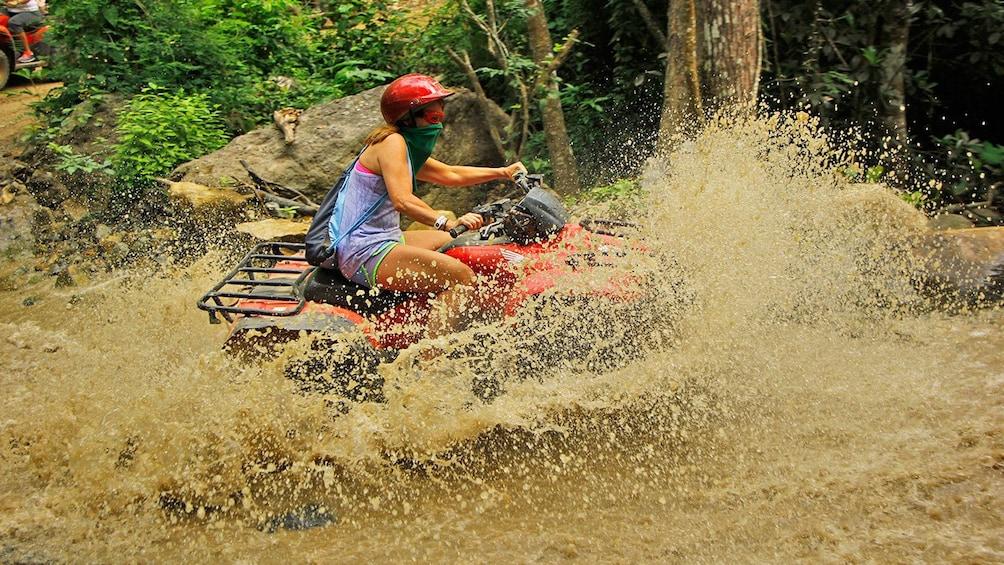 Show item 3 of 10. Woman on an ATV splashing through the river in Puerto Vallarta