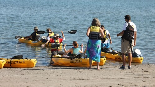 Instructor helping kayakers push off from the beach in Lorento