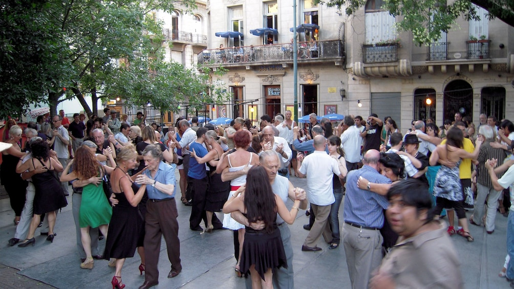 Show item 2 of 10. large crowd dancing at an outdoors public space in Argentina