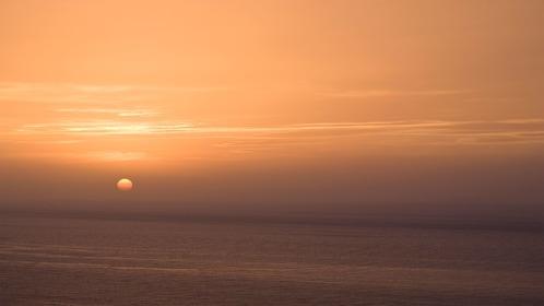 the sun setting on the ocean horizon in Greece