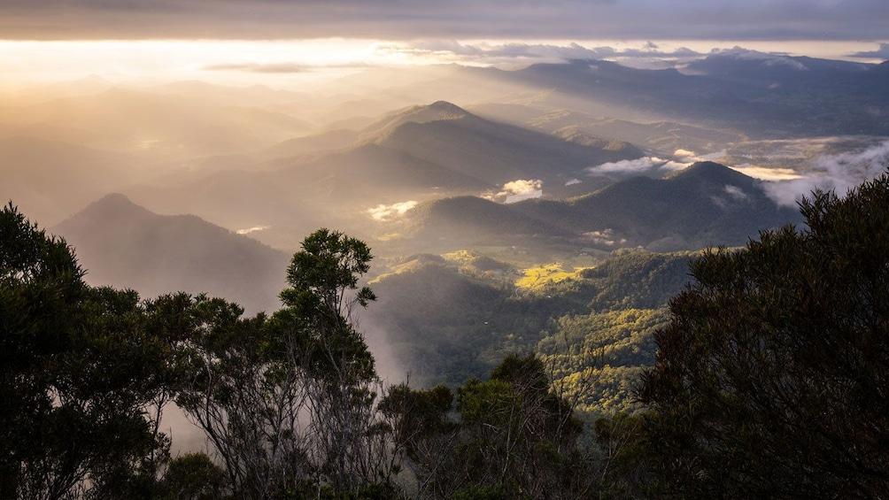 Show item 5 of 5. sunlight shining down on the mountainous landscape in Australia