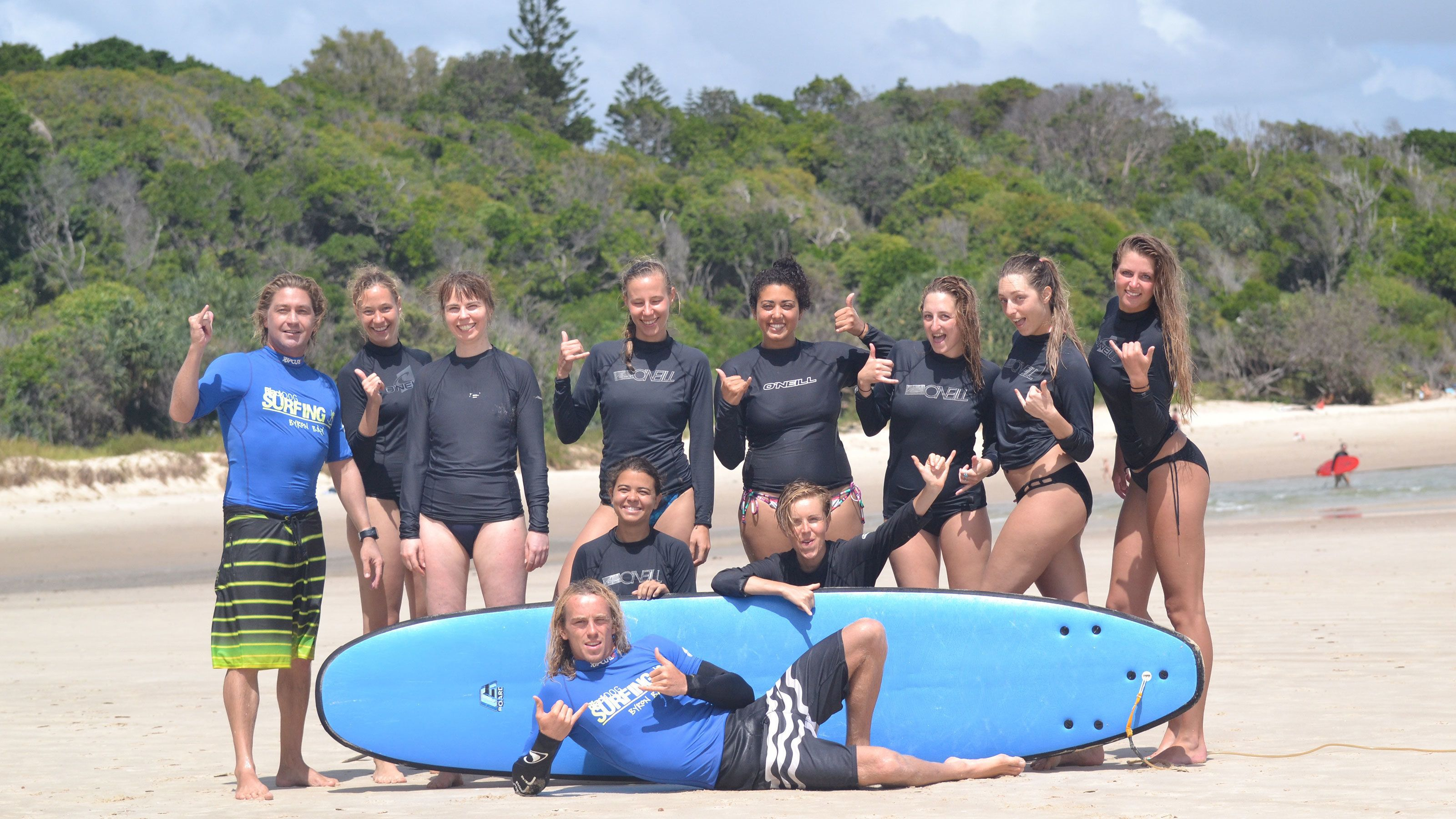 group of surfers posing at the beach in Australia