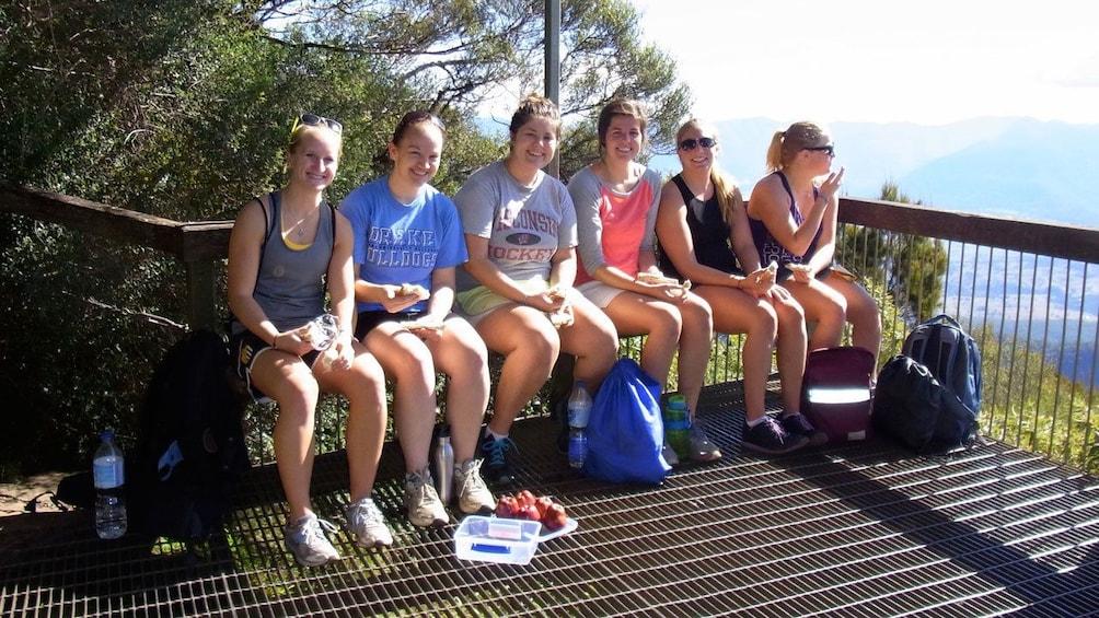 Show item 5 of 5. hikers taking a break sitting in the sunlight in Australia