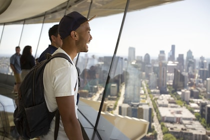 Guest enjoys views of downtown Seattle from the Space Needle glass floor - The Loupe.jpg
