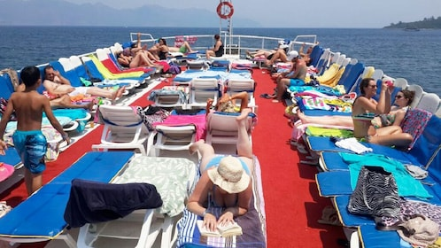 people lounging on deck of boat