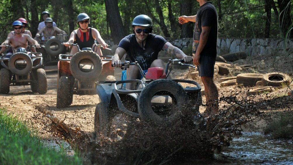Show item 5 of 5. group of ATV riders in muddy area