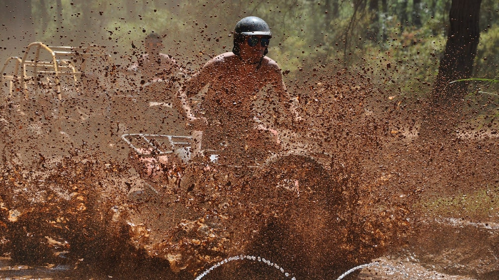 Show item 2 of 5. quad splashing through mud