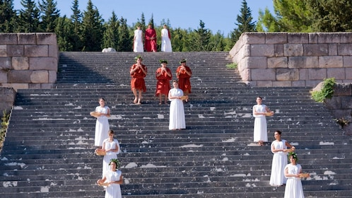 performers in white and red outfits on extensive stair case