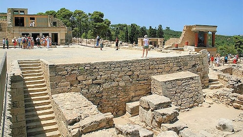 Tourists walking among the ruins of a palace in Knossos