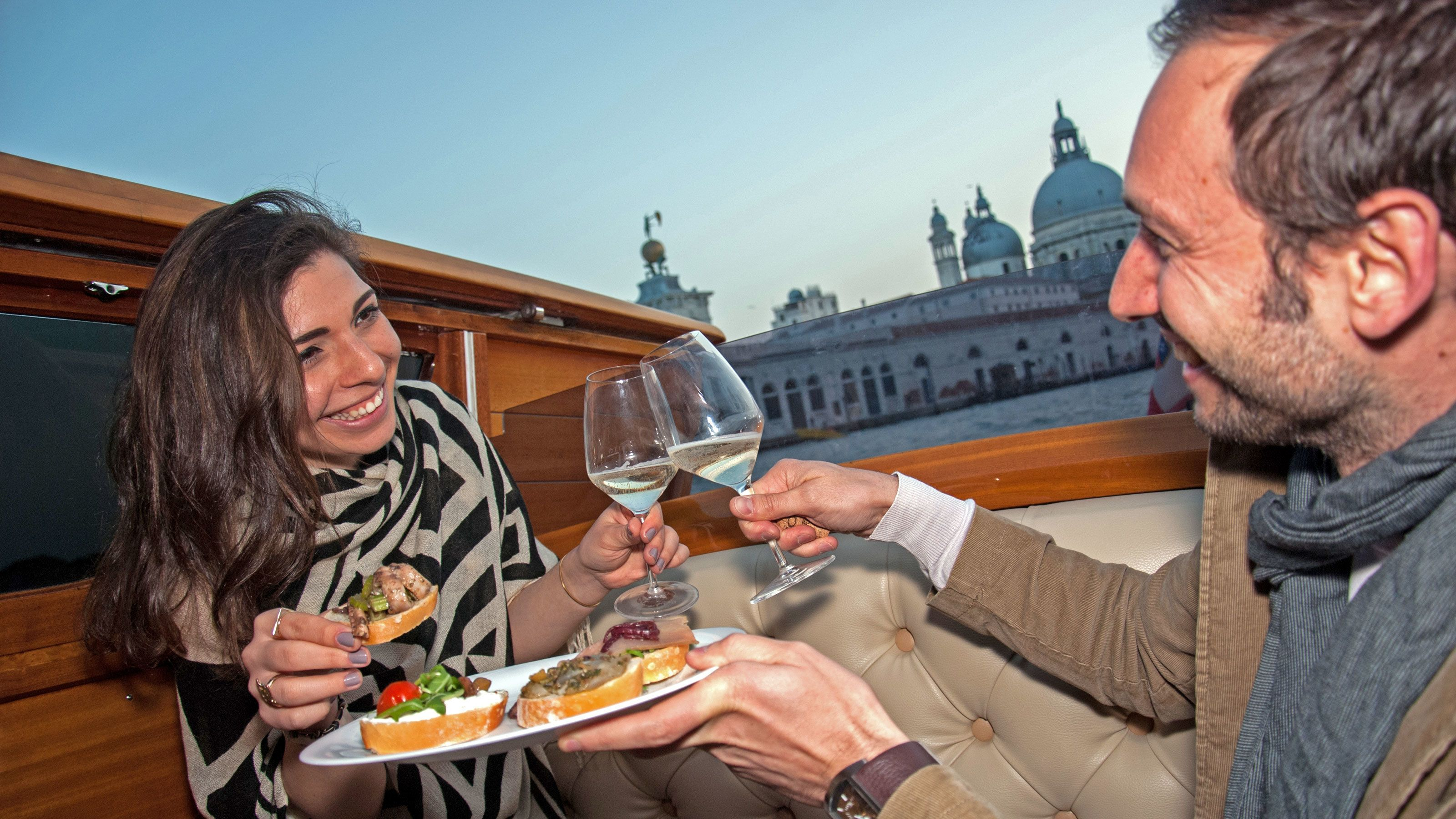 people snacking and drinking wine on boat