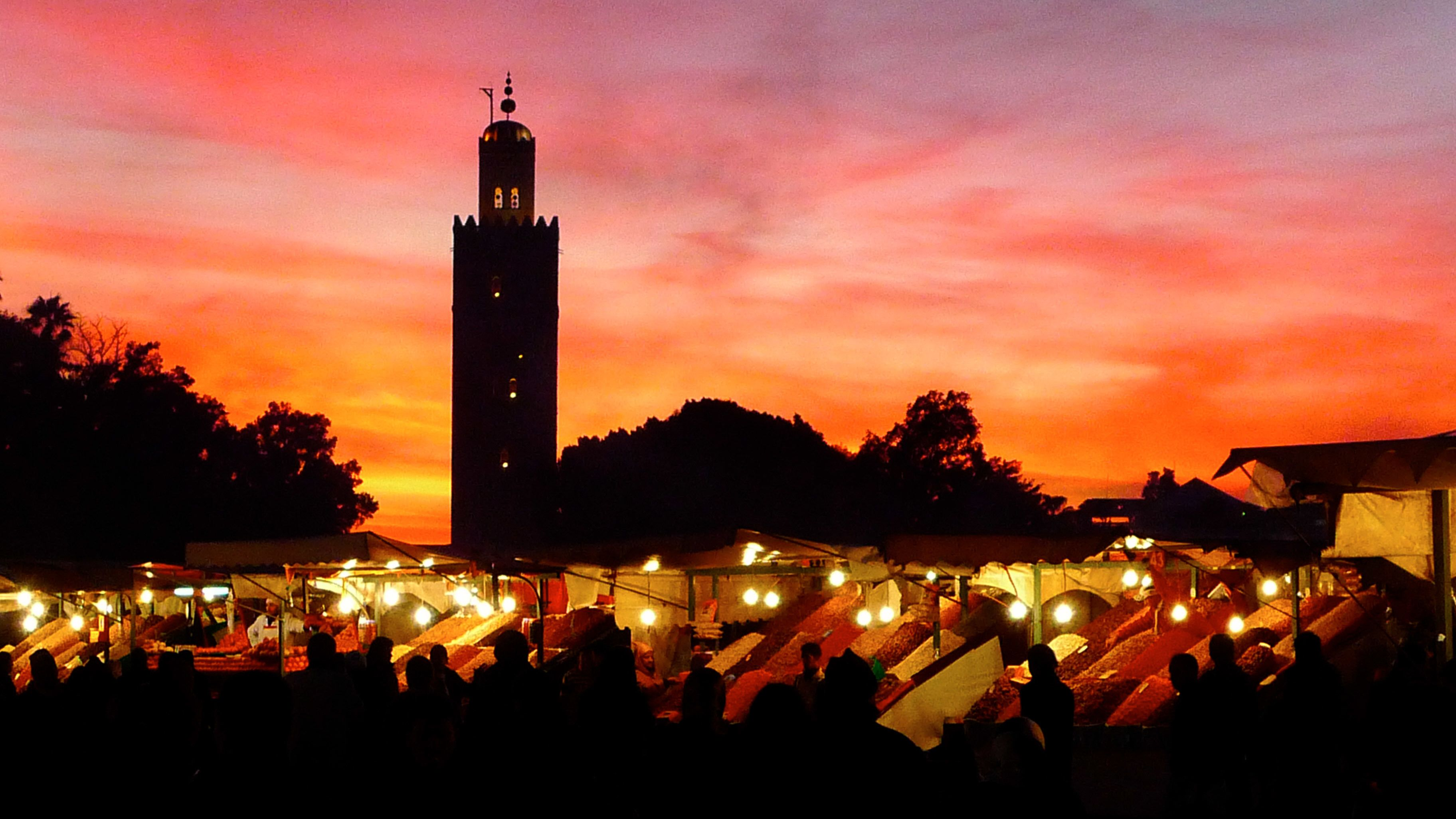 Market with silhouette of Koutoubia Mosque in the background at sunset in Marrakech