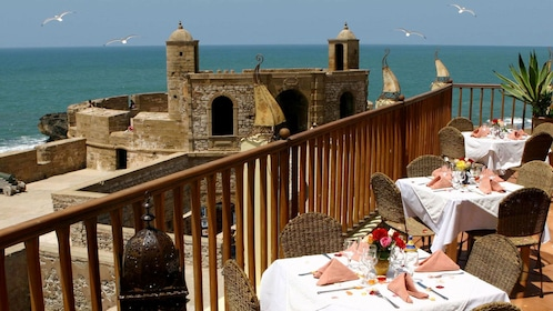 Outside dining on a terrace overlooking the ancient city walls and coastline in Essaouira
