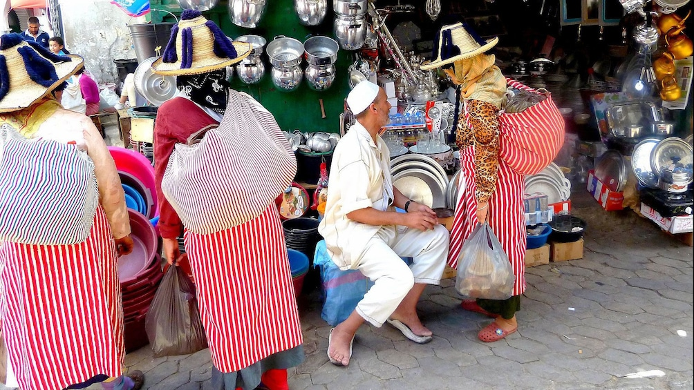 Show item 1 of 5. Locals haggling with a street vendor in Marrakech