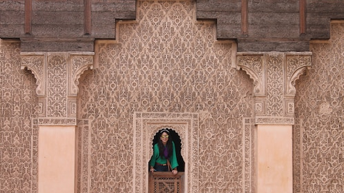 Woman peering out of her window of a Moroccan apartment in Marrakech
