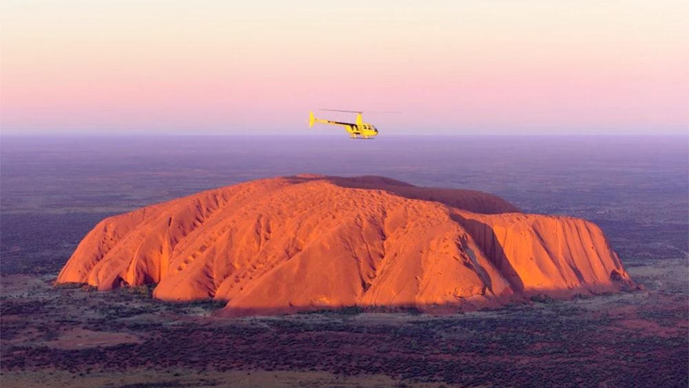 helicopter flying towards a large desert mountain in Australia