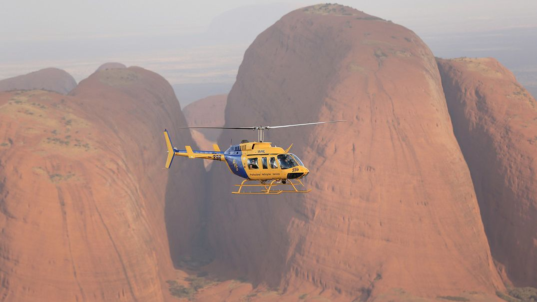 helicopter flying over red rocky cliffs in Australia