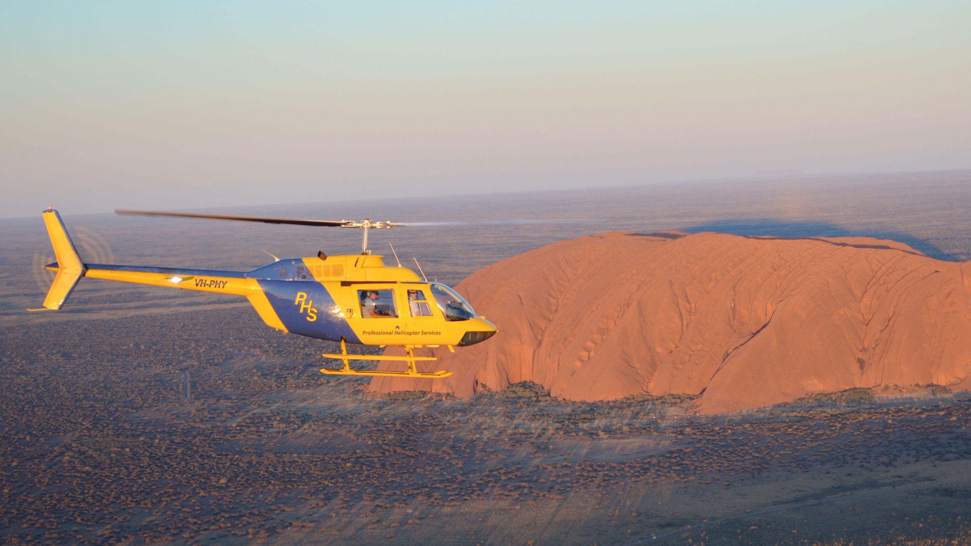 helicopter flying above the dry desert landscape in Australia