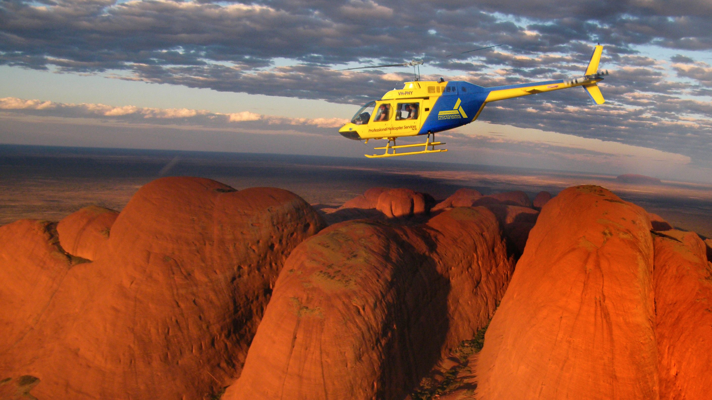 helicopter flying over red rock mounds in Australia