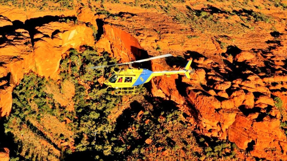 Show item 5 of 5. helicopter flying over red rocky cliffs in Australia