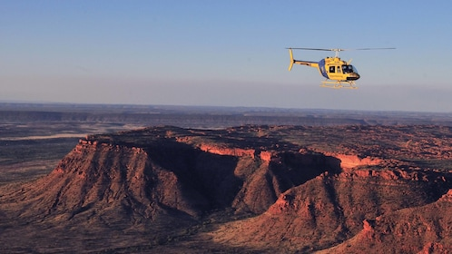 helicopter flying over red rock mountains in Australia