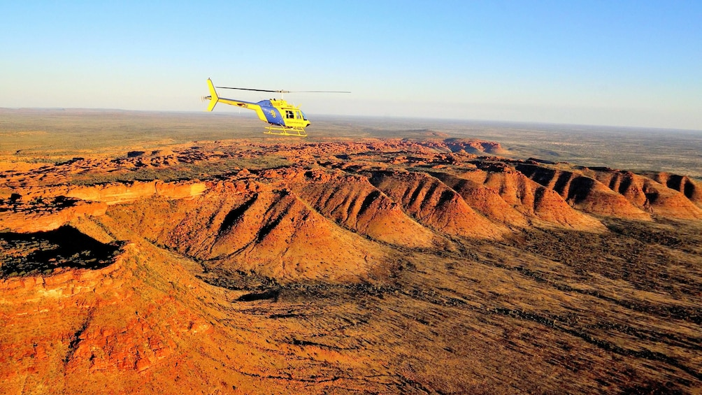 Show item 1 of 5. helicopter flying over a red desert in Australia
