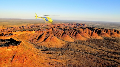 helicopter flying over a red desert in Australia