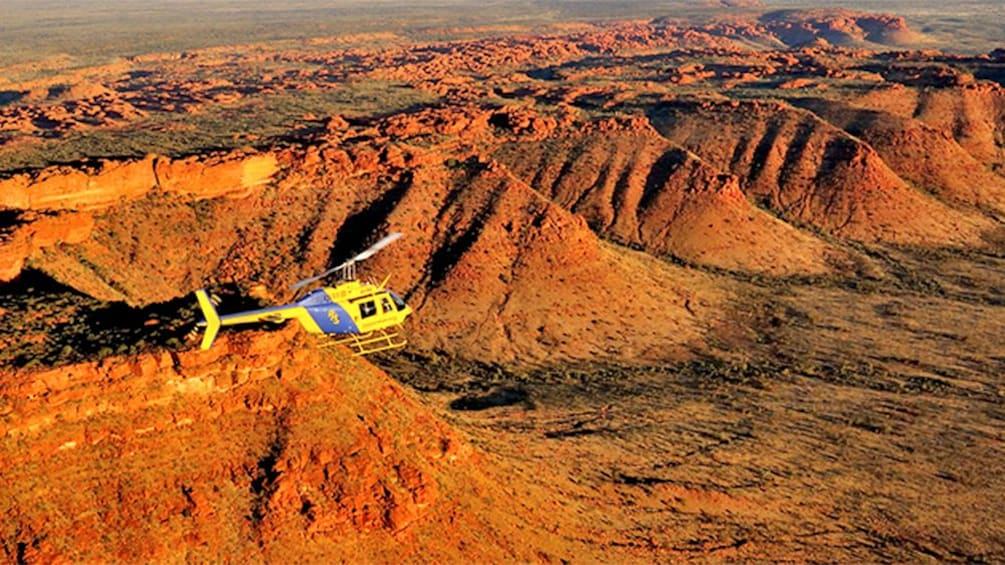 Show item 2 of 5. helicopter flying over a mountainous desert landscape in Australia